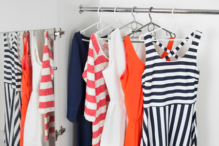 ropa de verano: a series of bright modern fashion womens dresses on hangers in a white cupboard for summer and spring