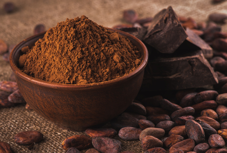 crude dark cocoa powder in a brown ceramic bowl, raw cocoa beans in the peel and raw chocolate on sacking close up, ingredients for preparing chocolate and sweets Foto de archivo