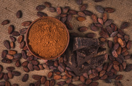 crude dark cocoa powder in a brown ceramic bowl, raw cocoa beans in the peel and raw chocolate on sacking close up, top view, ingredients for preparing chocolate and sweets