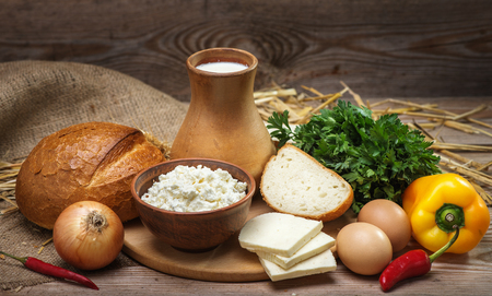 Farmers rustic natural organic foods, balanced diet, cooking, culinary, food concept, dairy products, bread, cheese, cottage cheese, eggs, onions, milk on the old wooden background
