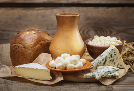 bread mold: Rustic natural dairy products, whole milk, cottage cheese, cut slices of blue cheese with mold, mozzarella cheese, Camembert, rustic bread, burlap, straw on the old wooden background