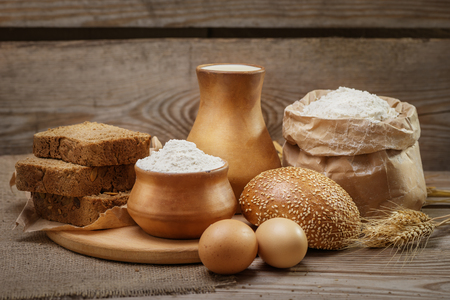 Ingredients for baking bread and pastry, milk, wheat flour, eggs, bun with sesame, rustic bread, cut into pieces, ears of wheat on the old wooden background