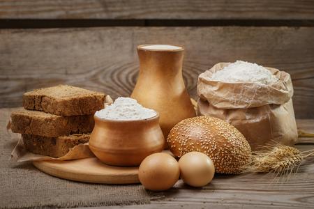 pasteles: Ingredientes para la cocci�n de pan y pasteler�a, leche, harina de trigo, huevos, pan con s�samo, pan r�stico, cortado en trozos, espigas de trigo en el fondo de madera vieja