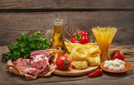 Ingredients for cooking pasta, Italian food, meat and spices, tomato, bell pepper,  olive oil and parsley