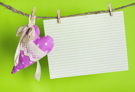 message card with handmade heart of the cloth with polka dots on a rope with clothespins, greeting and love concept,  happy birthday, Congratulations on March 8