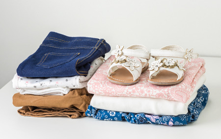 baby wardrobe: stack of clean baby clothes and the little girls white sandals in white wardrobe Stock Photo