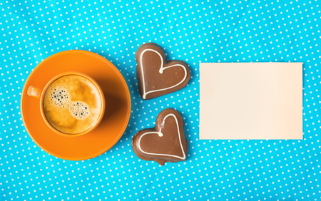 cup with coffee  espresso, tablet for text and two chocolate marzipan candy hearts on a bright blue background