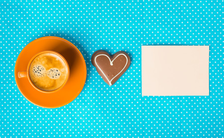 have on: cup with coffee  espresso, tablet for text and chocolate marzipan candy heart on a bright blue background
