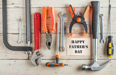 Greeting Card to Happy Father\'s Day, set of different tools: a hammer, Hand saw, pliers, wrench, screwdriver, various spanners, clamp on a wooden background