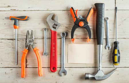 jornada de trabajo: Tarjeta de felicitaci�n, el d�a de padre feliz, cumplea�os del pap�, el concepto, un conjunto de herramientas de carpinter�a diferentes: un martillo, Sierra de mano, alicates, llave inglesa, destornillador, varias llaves, abrazadera sobre un fondo de madera y la tableta