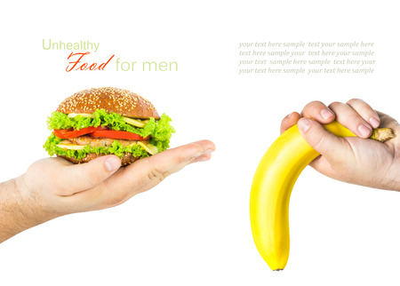 impotent: A mans hand holding a burger, the other mans hand holding a banana Stock Photo