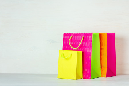 Three bright multi-colored shopping bags on a white wooden background