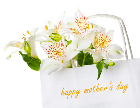 mothers group: Beautiful bouquet of white alstroemeria flowers in a paper bag with the inscription happy mothers day