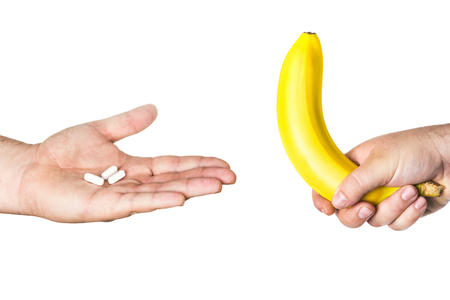 impotent: white pills and big banana in man hands isolated on white background