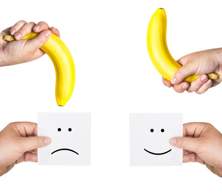 xxx: two mens hands holding smiley and sad faces,  two hands hold the big bananas up and down