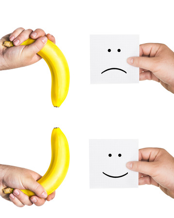 medium size: two mens hands holding smiley and sad faces, two hands hold the big bananas up and down Stock Photo