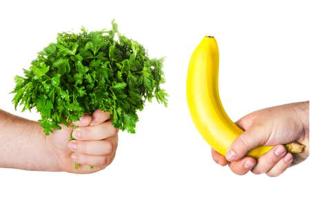 potency: mans hand holding a large bunch of parsley, fresh herbs, the other mans hand holding a banana Stock Photo