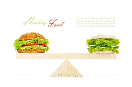 junk food: classic burger and a healthy burger with wholegrain cereal crispbreads, vegetables, herbs and cheese on scales. Isolated on white background