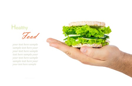 vegeterian: The concept of a healthy food, diet, losing weight, vegeterian. Mans hand holding a healthy burger with wholegrain cereal crispbreads, vegetables, herbs and cheese. Isolated on white background