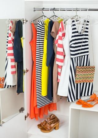 ropa de verano: Conjunto de brillantes colores de ropa de moda femenina en las perchas para la primavera y el verano armario, bolso, sandalias en el gabinete blanco