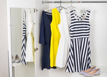 a series of bright modern fashion women\'s dresses on hangers in a white cupboard for summer and spring