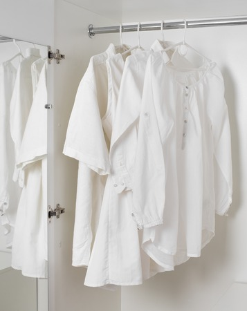 set of white clean ironed clothes hanging on hangers in a white cabinet
