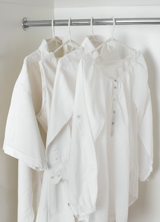 ironed: set of white clean ironed clothes hanging on hangers in a white cabinet