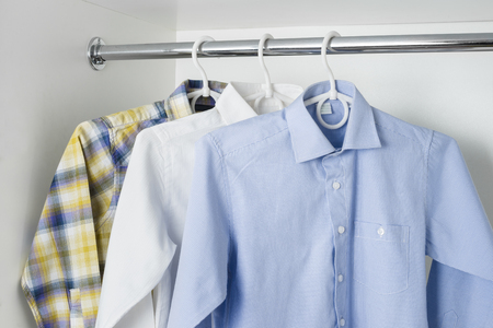 ironed: white, blue and checkered clean ironed mens shirts hanging on hangers in the white wardrobe