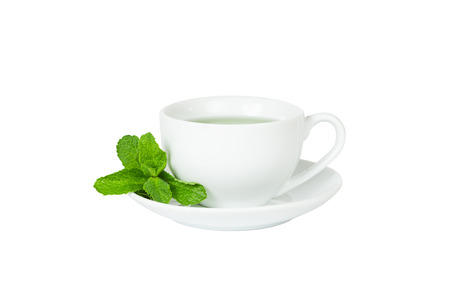 cup and saucer: cup of mint tea, white cup, saucer and a sprig of fresh mint isolated on white background Stock Photo