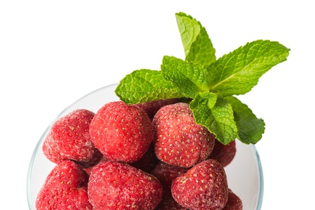 Frozen strawberries in a ice-cream bowl, a sprig of fresh mint top view on a white background