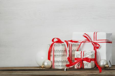 moños navideños: regalos hechos a mano de vacaciones con cintas rojas y blancas, bolas para el árbol de Navidad en un fondo de madera