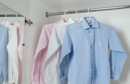 ironed: white, blue and pink clean ironed mens shirts hanging on hangers in the white wardrobe