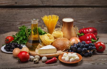 イタリア料理の古い木製の背景、野菜、パスタ、フルーツ、卵、乳製品、バランスの取れた食事の概念は、成分の異なる食品のセット