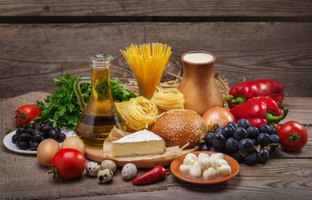 Set of different foods on the old wooden background, vegetables, pasta, fruit, eggs, dairy products, the concept of a balanced diet, the ingredients for Italian food Stock Photo