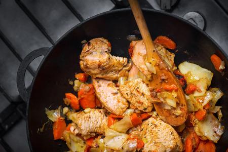 carnes y verduras: Filete de pavo asado con verduras en una sartén en un plato, una cuchara de madera mezclas para carnes a la parrilla, vista desde arriba, de cerca Foto de archivo