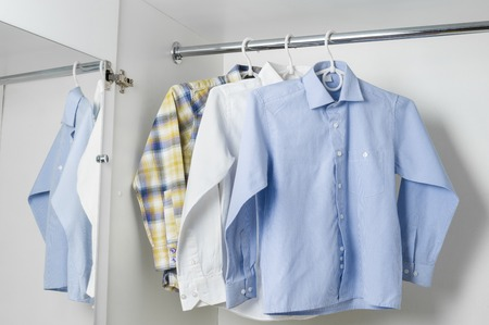 formal dressing: blue and checkered clean ironed men shirts hanging on hangers in the white wardrobe