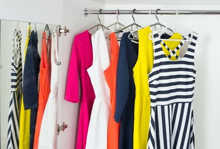woman closet: a series of bright modern fashion womens dresses on hangers in a white cupboard for summer and spring