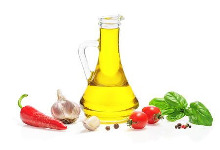 Olive oil in a glass jug, red hot chili peppers, cherry tomatoes, allspice, a mixture of peppers, basil, garlic isolated on a white background. 免版税图像