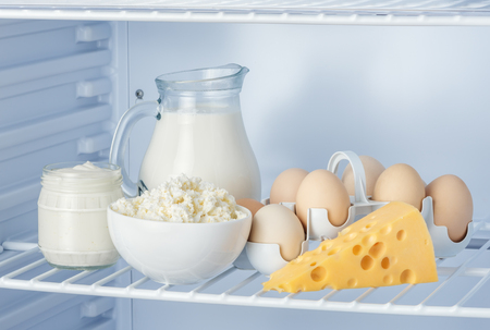 eggs and tasty healthy dairy products in the refrigerator: sour cream in the bank, cottage cheese in  bowl, eggs, cheese and milk in a jar Foto de archivo