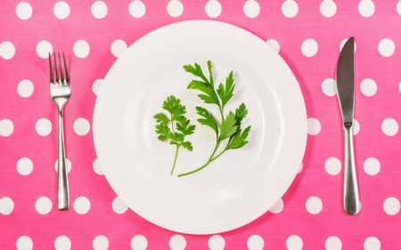 potherb: concept of healthy eating,  lose weight, vegetarian, vegan, raw food, potherb in the diet, sprig of fresh parsley, cilantro on a plate, fork and knife on a bright pink tablecloth with white polka dots