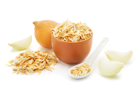 Dried onions in a white ceramic spoon, chopped fresh onion  isolated on white background closeup