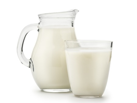 Natural whole milk in a jug and a glass isolated on a white background closeup