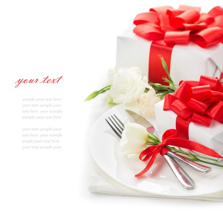 lady s: The concept of the holiday menu for Womens Day March 8, Mothers Day, St. Valentines Day, birthday, gifts with red ribbons, white flowers eustoma, a plate with knife and fork on a white background