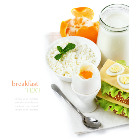 tex: Delicious healthy breakfast of fresh products, yogurt, cottage cheese, boiled egg in the stand, sandwiches with cheese, tangerines, composition on a white background, space for tex