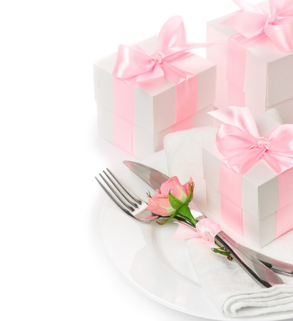 birthday present: The concept of the holiday menu, knife, fork and a napkin on a plate with floral decoration, gifts with pink ribbon isolated on white background Stock Photo