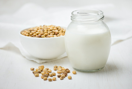 Soy milk in a glass jar, soybeans on a white table 免版税图像