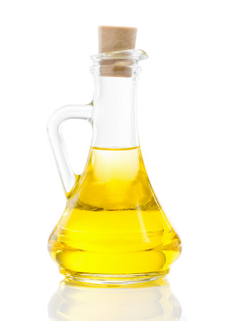 Glass jug with vegetable oil, sunflower, sesame, linseed, cedar, olive oil, walnut oil close up isolated on white background
