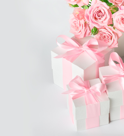 Festive composition of flowers and gifts on a white table