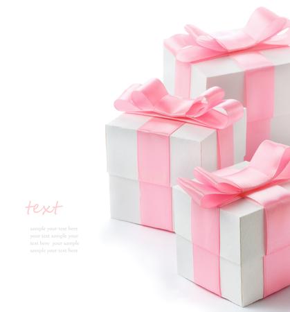 Geschenk witte doos met roze satijnen lint op een witte achtergrond, gefeliciteerd met Dag van de Vrouw, dag van het mamma, Valentijnsdag, gelukkige verjaardag