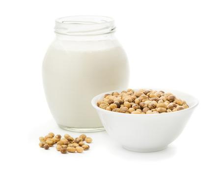leche de soya: La leche de soya en un frasco de vidrio y la soja aislada en el fondo blanco